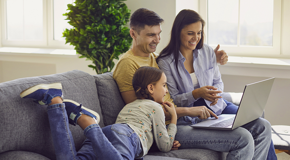 Happy family looking at their home inspection report on a laptop