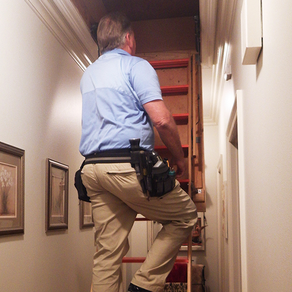 Kary climbing a ladder to an attic while preforming home inspection services