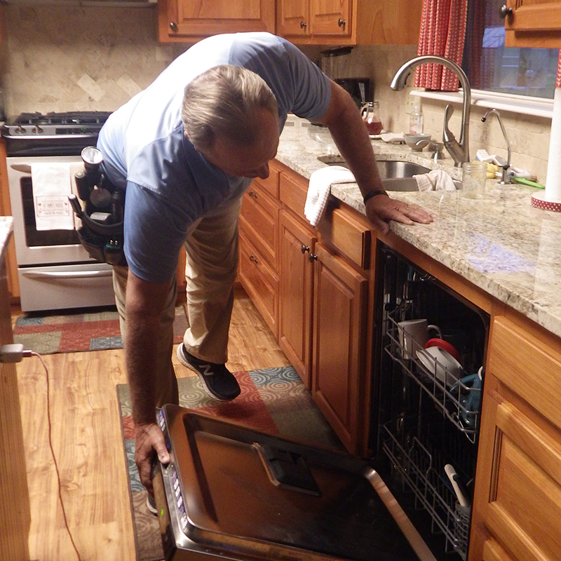 Kary in a kitchen inspecting the appliances while preforming home inspection services